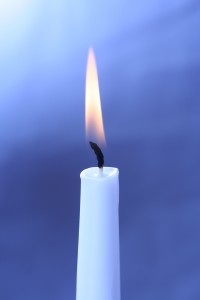 burning white candle on a blue background